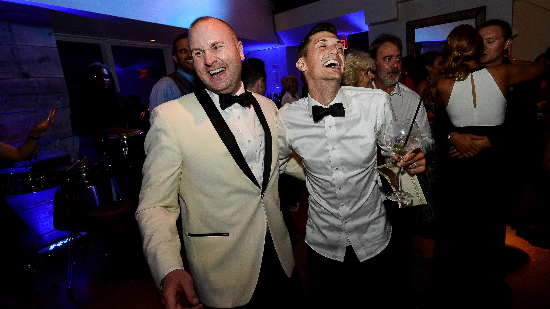 grooms laughing during reception